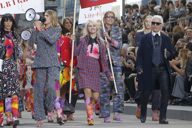 German fashion designer Karl Lagarfeld, right, acknowledges applause as models stage a fake demonstration, with Cara Delevingne, left with a megaphone, as part of Chanel's Spring/Summer 2015 ready-to-wear fashion collection presented in Paris, France, Tuesday, Sept. 30, 2014. (AP Photo/Thibault Camus)